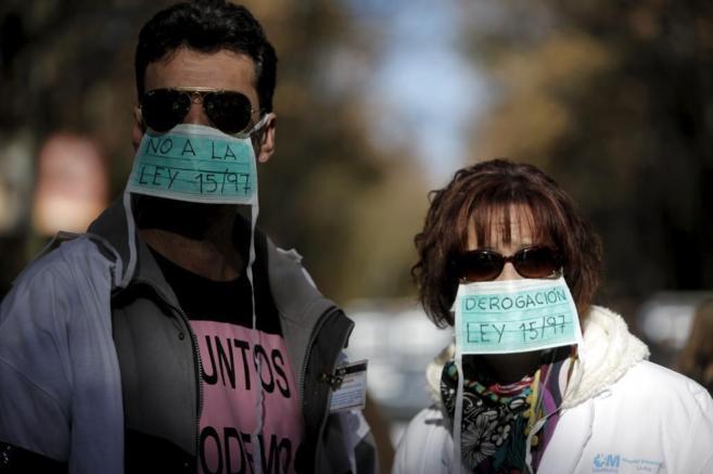Dos manifestantes exigen la derogación de la ley de privatización.