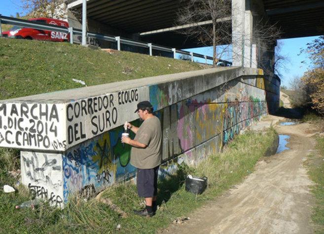 Un activista pinta en un muro la convocatoria de la marcha senderista...