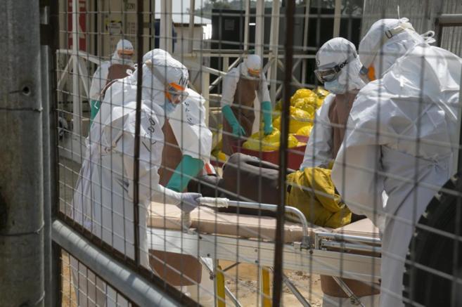 Trabajadores sanitarios británicos transportan a un paciente de...