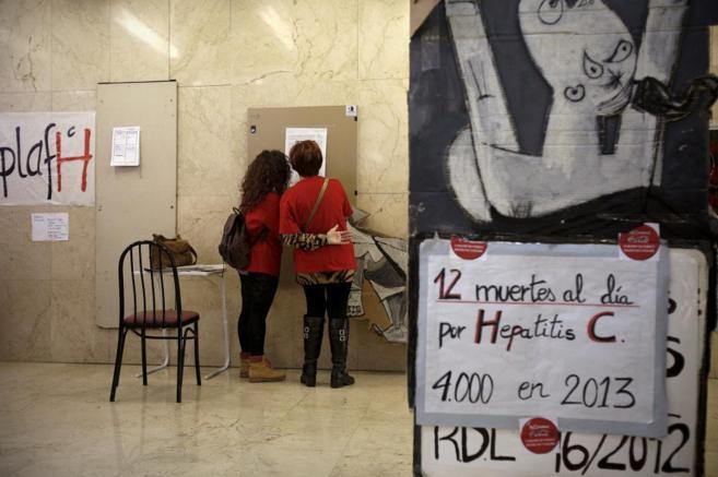 Dos mujeres leen las protestas de los pacientes con hepatitis C...