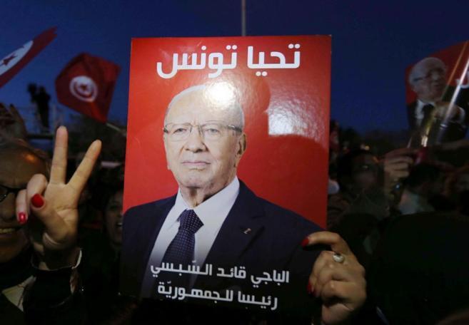 Una simpatizante del nuevo presidente tunecino hace el gesto de la...