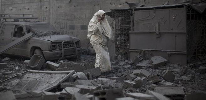 Una mujer camina entre los escombros dejados por un bombardeo en Gaza.