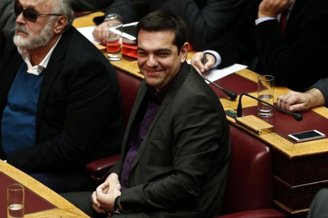 El líder de Syriza, Tsipras, sonríe durante la votación en el...