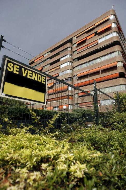 Viviendas con un cartel de 'Se vende' en la valla de la...