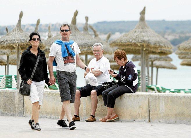 Una pareja de turistas paseando por Playa de Palma el pasado verano.