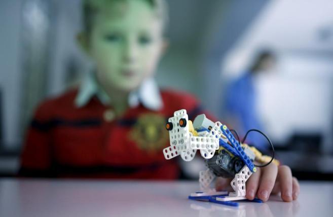 Un alumno  muestra una de sus creaciones.