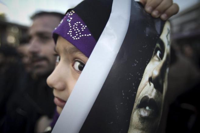 Una niña iraní muestra una foto de Obama en Teherán.