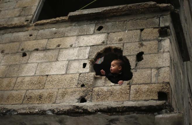 Un niño palestino observa a través del agujero de una pared...