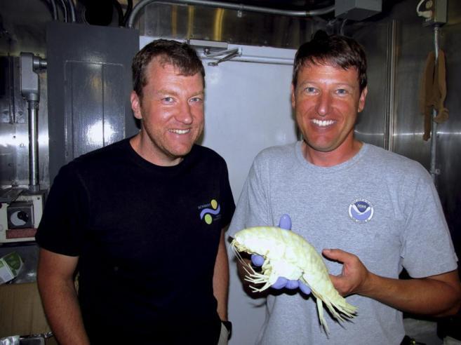 Dos miembros del equipo, con un crustáceo recogido por un submarino.