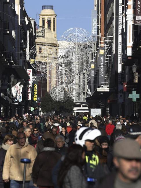 Cientos de personas pasean por la calle Preciados de Madrid.