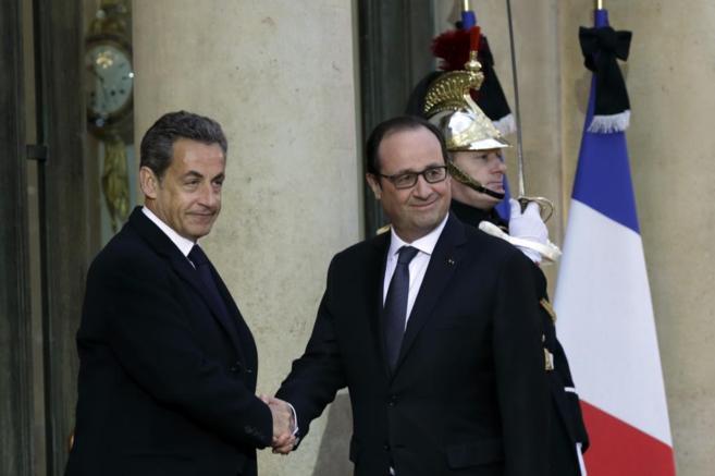 El presidente francés, Hollande (dcha.), saluda al ex mandatario...