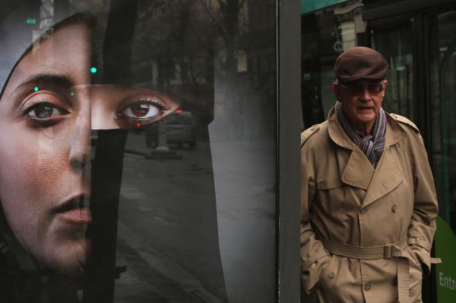 Un hombre camina junto a un cartel publicitario con el rostro de una...