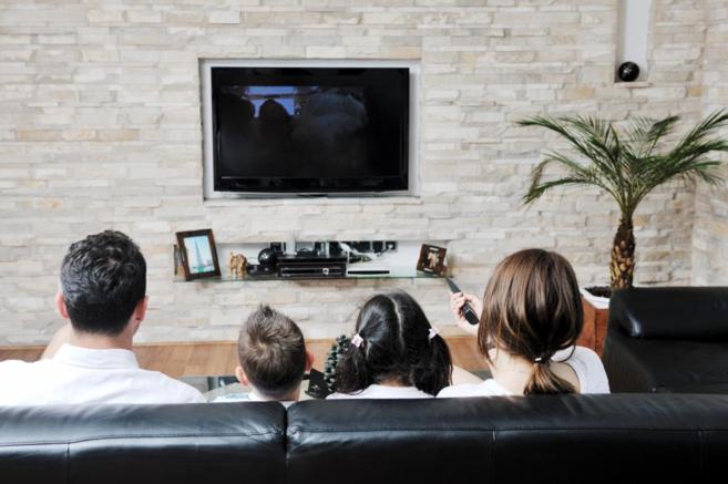 Una familia visiona un programa de televisión en su casa.