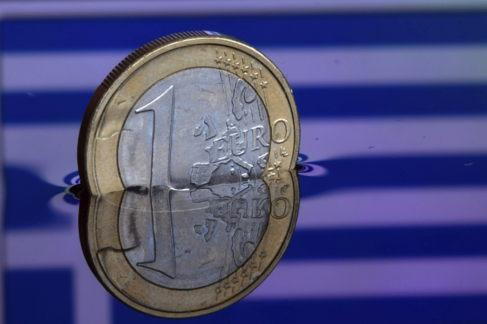 Una moneda de euro semisumergida en agua.