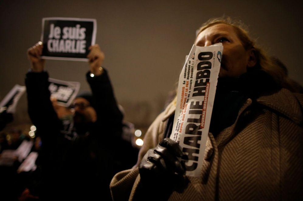 Un hombre con un ejemplar del semanari Charlie Hebdo durante la...