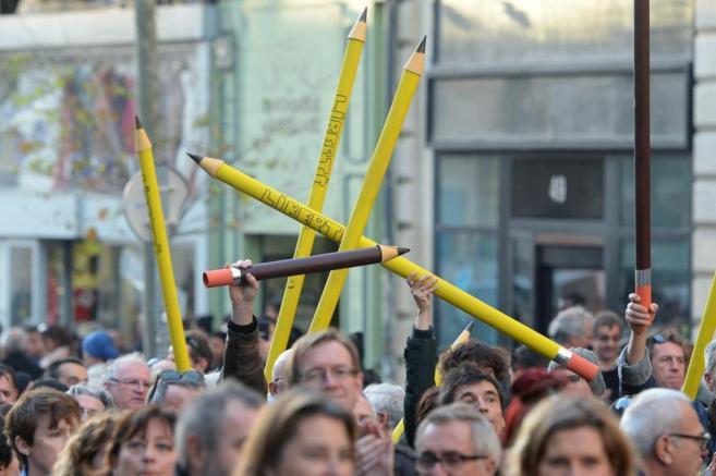 Un grupo de manifestantes sostiene lápices gigantes en los que se lee...