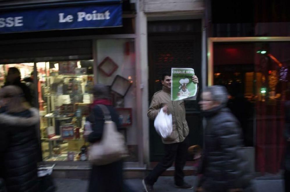 Un hombre muestra su ejemplar del último número de  Charlie Hebdo al...