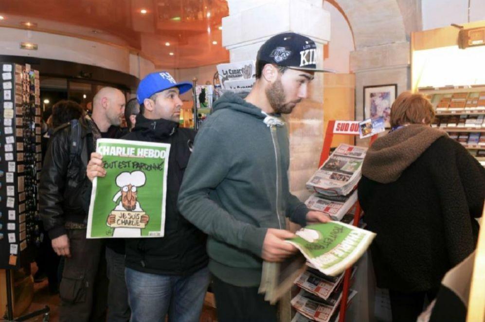 Varias personas sujetan un ejemplar de Charlie Hebdo en la cola de un...