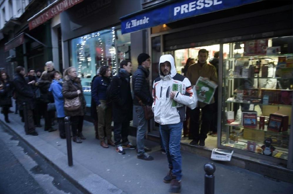 Dos hombres salen de un quiosco de París portando sus ejemplares de...