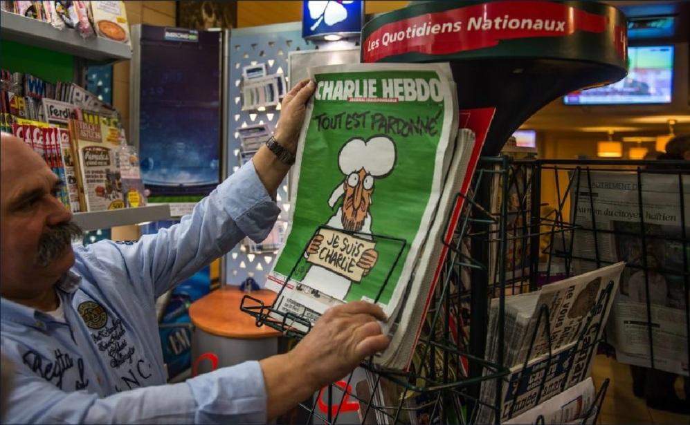 Un hombre coge un número del último ejemplar de Charlie Hebdo en un...