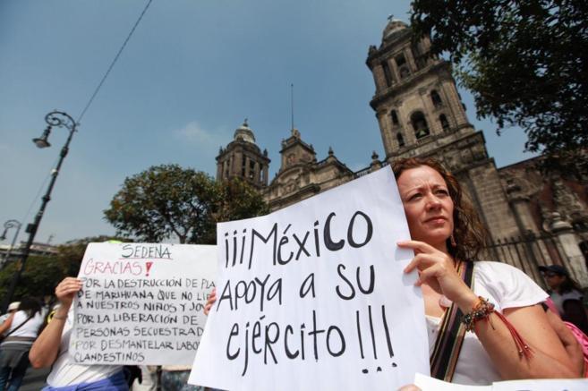 Una mujer sujeta un cartel de apoyo a los militares el pasado 11 de...