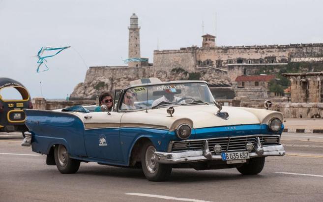 Dos turistas pasean en taxi por La Habana.