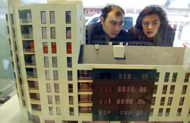 Imagen de archivo de una pareja mirando una promoción de pisos en el...