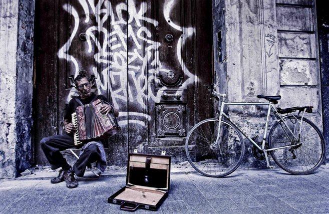Una persona toca el acordeón en una calle de Valencia.