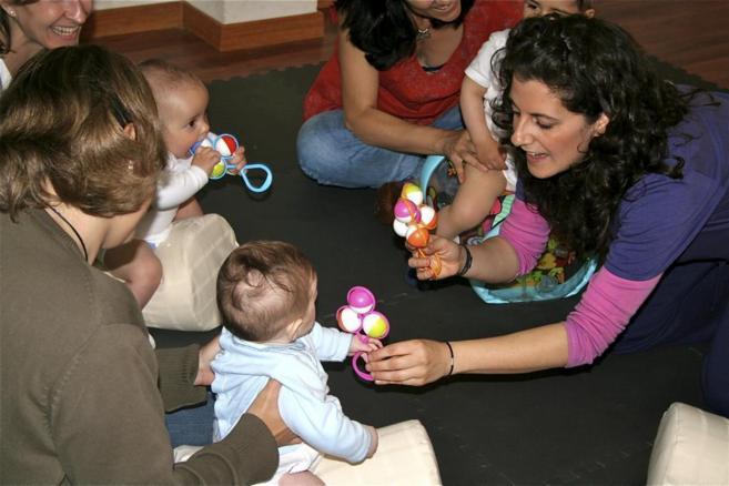 Un grupo de bebés juega con sus madres