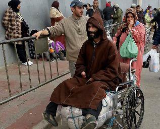 Un minusválido con un fardo en la silla de ruedas atraviesa la...