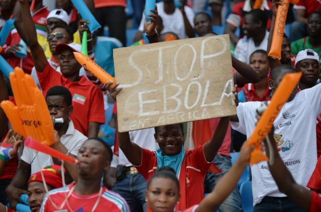 Una aficionada muestra un cartel pidiendo parar el ébola en África...