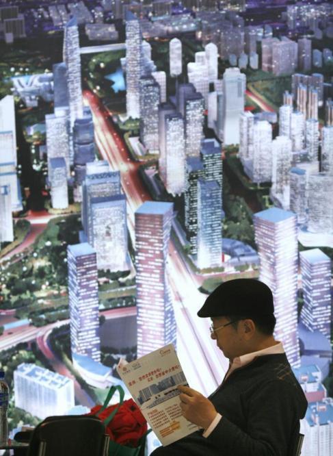 Un hombre consulta un folleto junto a un anuncio del Pekín...