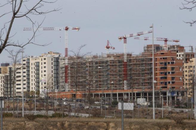 Imagen de archivo de varias grúas levantando edificios de pisos en...