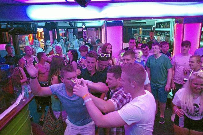Jóvenes británicos consumiendo alcohol en un local de Magaluf.