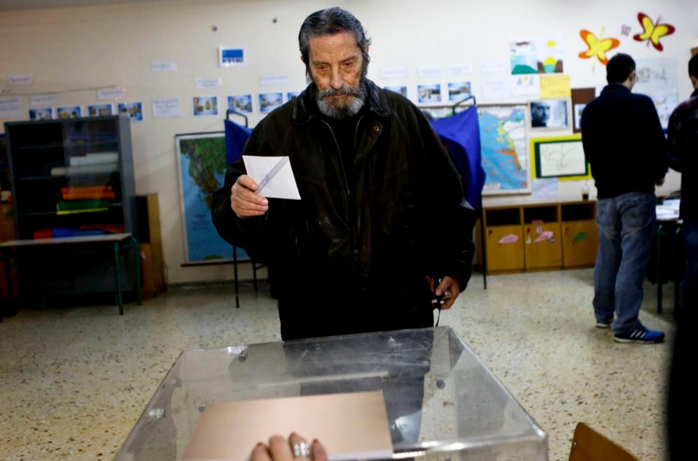 Un hombre, a punto de introducir su voto en la urna poco después de...