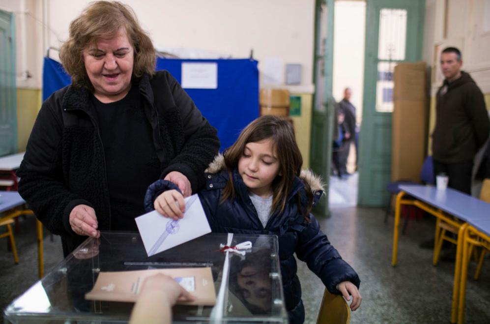 Una mujer vota 'ayudada' por su hija en Atenas.