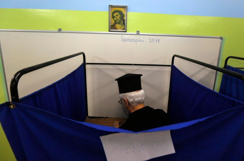 Un sacerdote ortodoxo elige su voto dentro de una de las cabinas de...