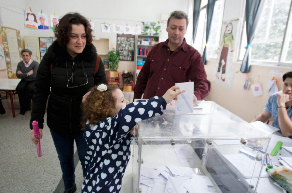 Una niña 'ayuda' a sus padres a votar en un colegio electoral de...