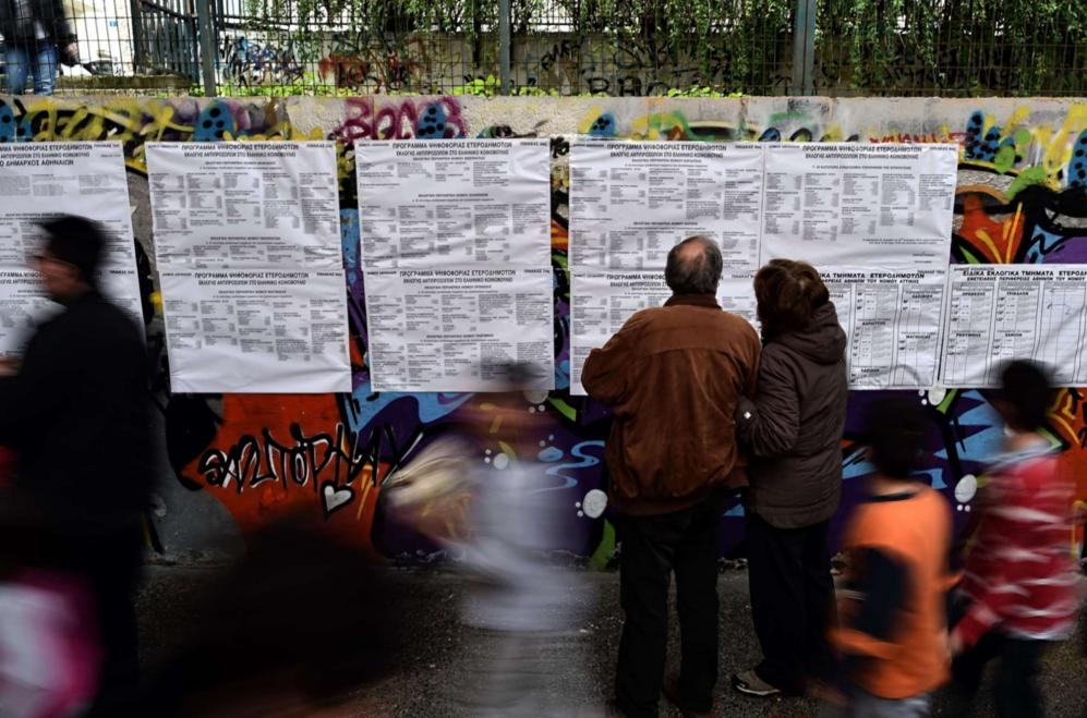 Una pareja comprueba sus datos a la entrada del colegio electoral en...