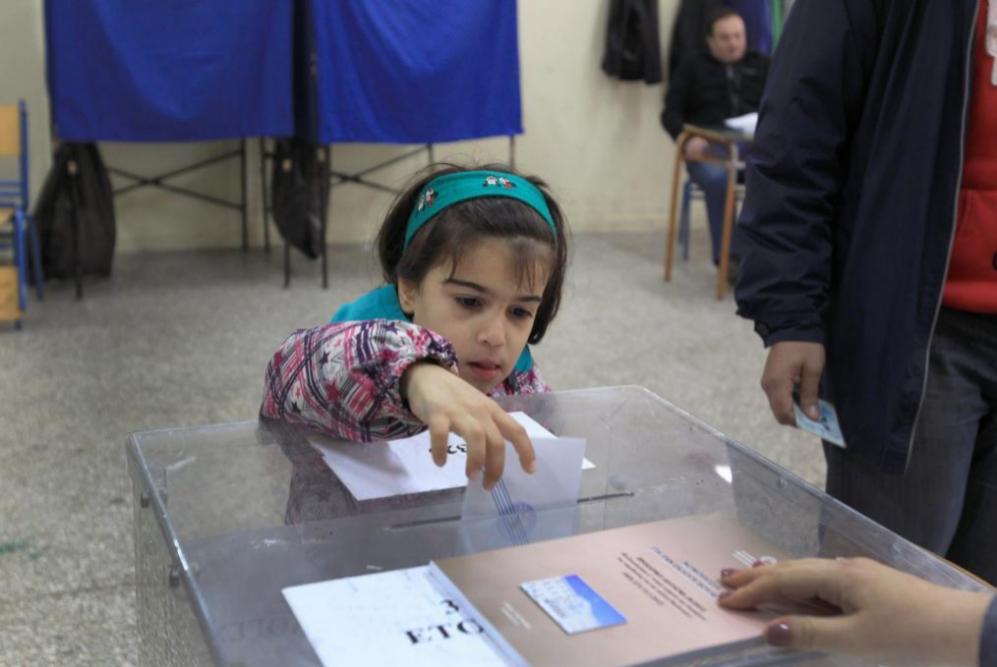 Una niña deposita en la urna el voto de su padre .