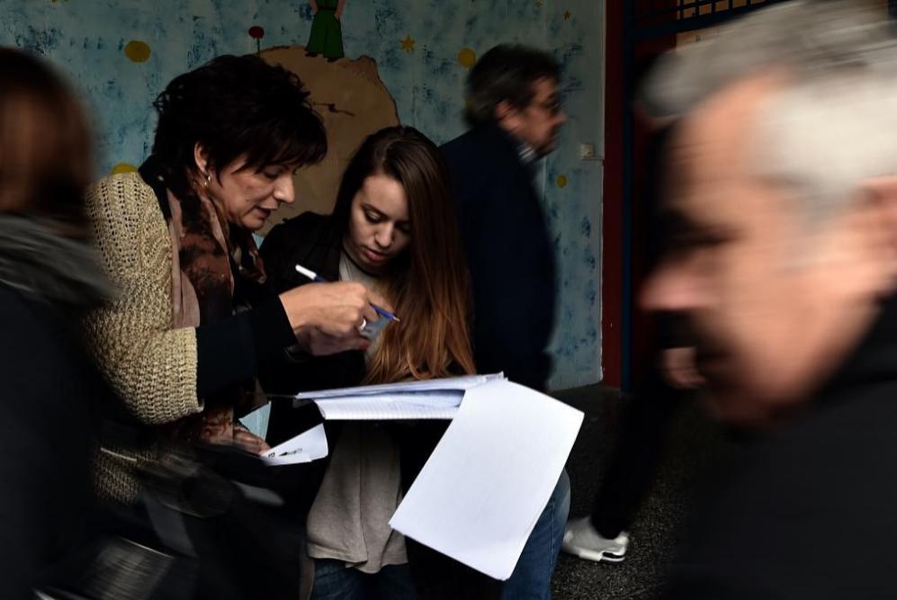 Comprueban las listas electorales en un colegio electoral en Atenas...