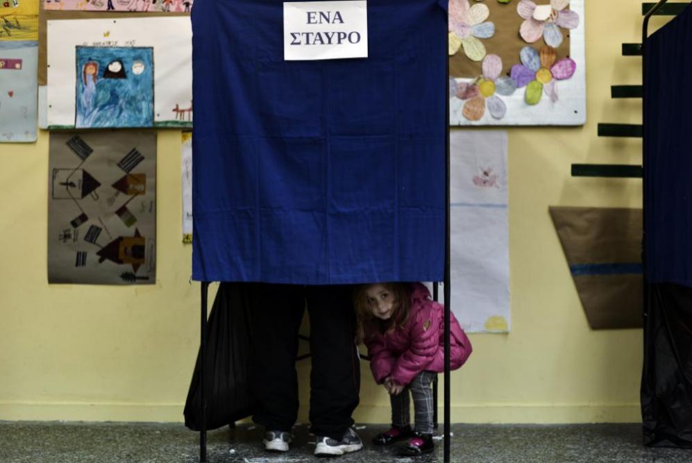 Una niña mira por una cabina de votación en un colegio electoral en...