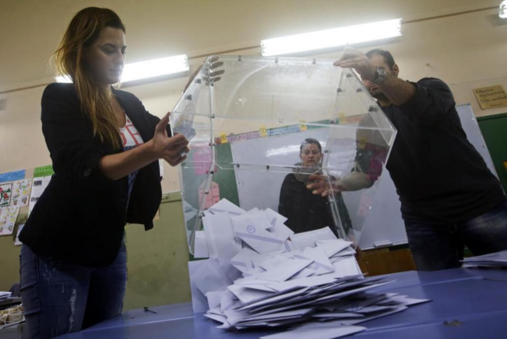 Las urnas se vacían después del final de la votación en un colegio...