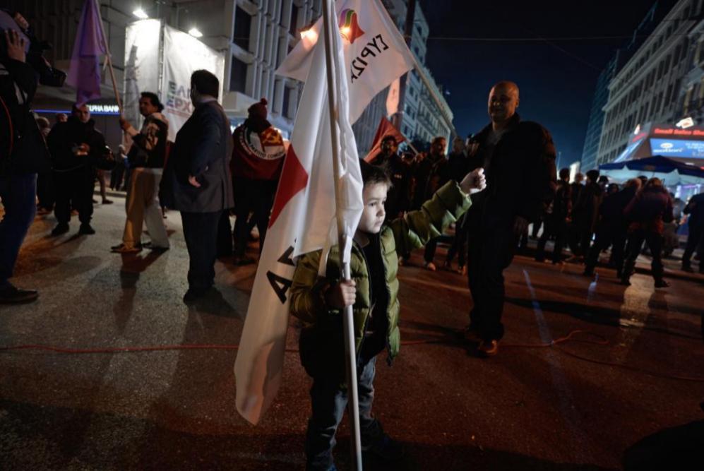 Un niño pequeño con una bandera de Syriza en una de las...