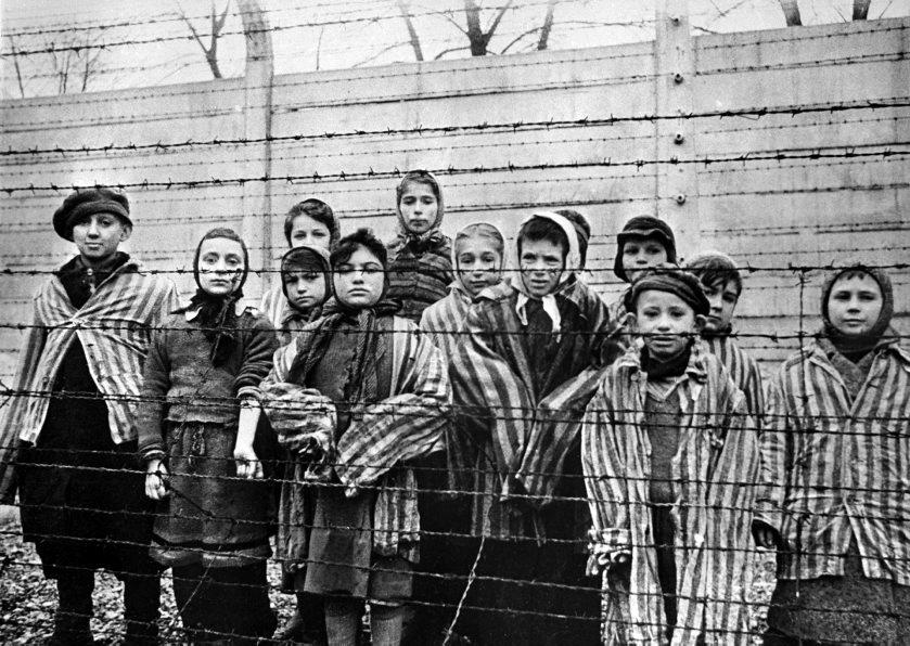 Un grupo de niños con los uniformes a rayas de los campos de...