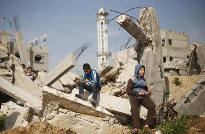 Varios niños palestinos reposan sobre los escombros de un edificio en...