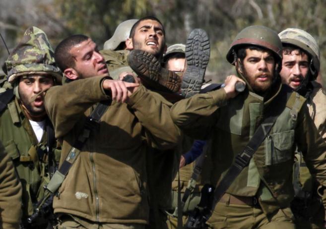 Soldados israelíes ayudan a un compañero herido durante los choques...