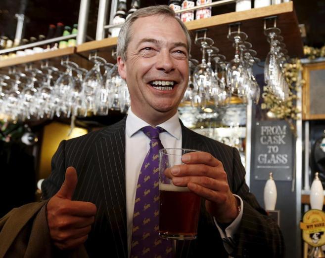 El líder del UKIP, Nigel Farage, posa con una pinta de cerveza en un...