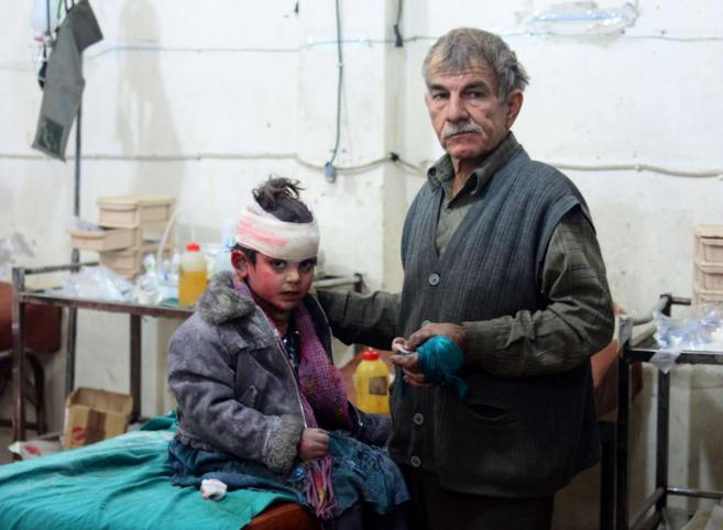 Un padre y su hijo esperan a recibir tratamiento en la ciudad de Douma