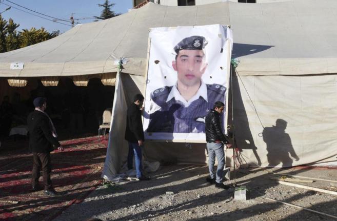 Familiares del piloto jordano Muaz Kasasbeh colocan una fotografía...